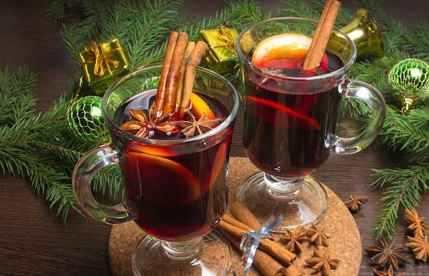 Kerst glühwein met kaneel en sinaasappel. op tafel liggen sparren twijgen en speelgoed