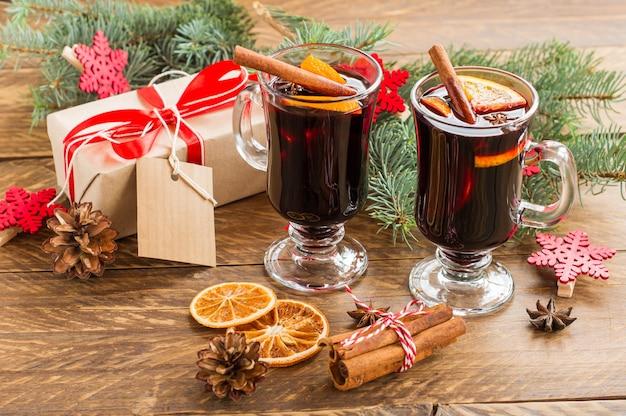 Kerst glühwein met kruiden en sinaasappelen op een rustieke houten tafel. traditionele warme drank met kerstmis met cadeaus