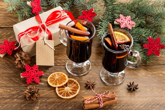 Kerst glühwein met kruiden en sinaasappelen op een rustieke houten tafel. traditionele warme drank met kerstmis met geschenken.