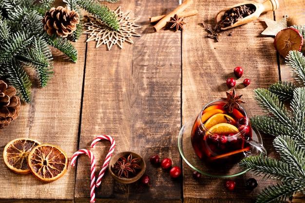 Kerst glühwein met kruiden op een houten rustieke tafel.