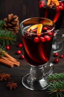 Kerst glühwein met sinaasappel en veenbessen. vakantie versierd met dennentakken en kruiden.