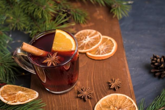 Kerst glühwein met sinaasappelplakken op basis van rode wijn met pittige kaneelstokjes, steranijs