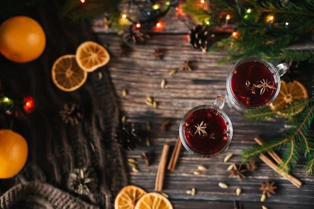 Kerst glühwein met stukjes sinaasappel, kaneel en andere kruiden op een houten tafel met een kerstboom