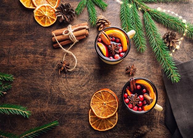 Kerst glühwein met veenbessen sinaasappel en kruiden in mokken op rustieke multiplex achtergrond