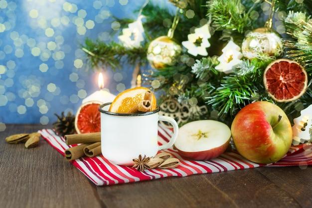 Kerst glühwein mocktail warme compote in een witmetalen mok met anijs kaneel sinaasappels