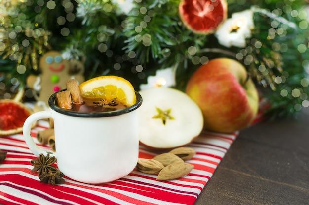 Kerst glühwein warme compote in een witmetalen mok met gedroogde vruchten anijs kaneel sinaasappels