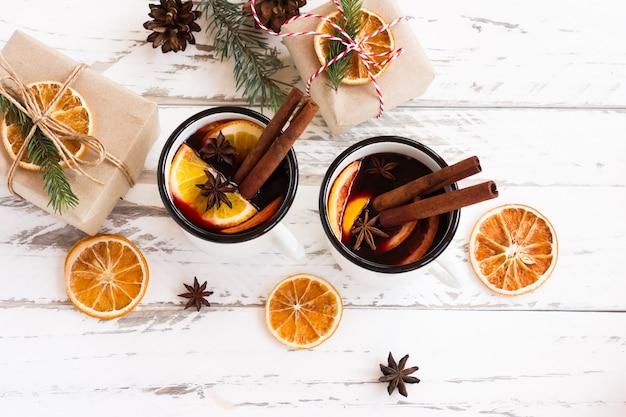 Kerst glühwein. warme rode winterpunch met fruit en kruiden. nieuwjaarssamenstelling met fruit en rustieke mokken. kerst stilleven. nieuwjaar thema.