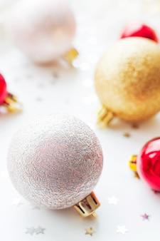 Kerst gouden en rode decoratieve ballen voor kerstboom gloeilampen en confetti.