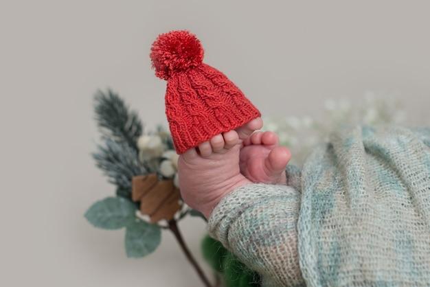 Kerst grap. winter concept, rode kerstmuts wordt op kleine vingers op de tenen op de voet van een pasgeboren baby