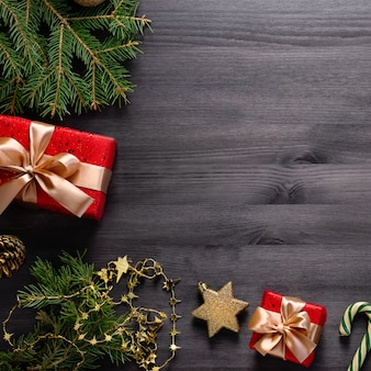 Kerst grens met dennen, cadeautjes, gouden elementen op zwart