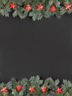 Kerst grens met dennentakken en rode kerstversiering op zwarte achtergrond.