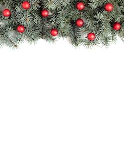Kerst grens met spar takken en rode ballen op een witte achtergrond.