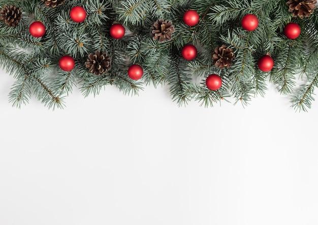 Kerst grens met spar takken, rode ballen en kegels op een witte achtergrond.