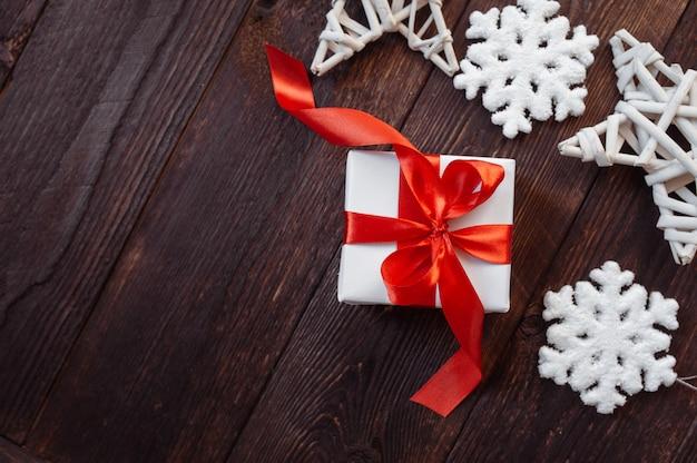 Kerst groeten kaart. witte geschenkdoos met rood lint en sneeuwvlokken