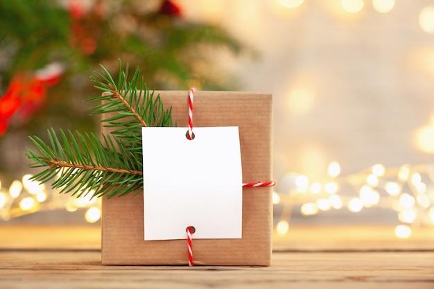 Kerst handgemaakte geschenkdoos met lege geschenkenkaart op een houten tafel.