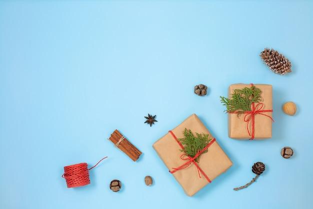 Kerst handgemaakte geschenkdozen versierd met ambachtelijk papier en sparren takken op blauwe achtergrond bovenaanzicht.