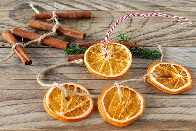 Kerst handgemaakte natuurlijke decoraties. garland en dennenboom speelgoed gemaakt van gedroogde plakjes sinaasappel op houten tafel. winter stilleven samenstelling.