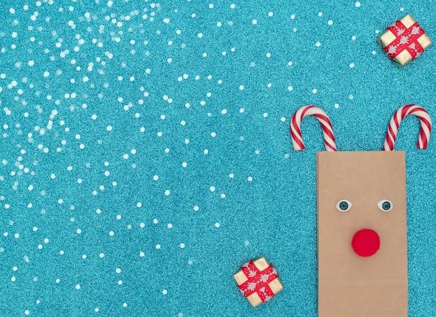 Kerst hert gemaakt van ambachtelijke tas en twee kerststokken met geschenkdozen op blauw