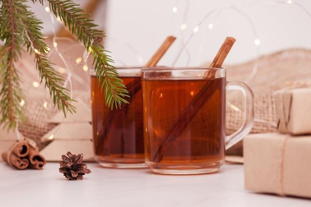 Kerst hete thee in glazen beker op witte houten tafel met kerstversiering.