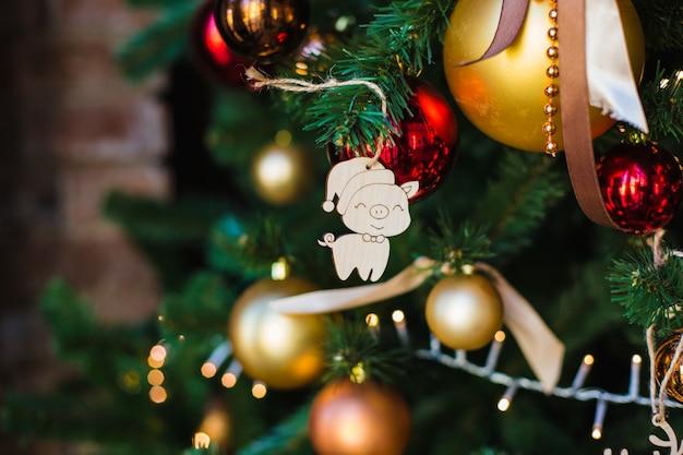 Kerst houten speelgoed in de vorm van een symbool van het naderende jaar-varken-opknoping op een feestelijke kerstboom