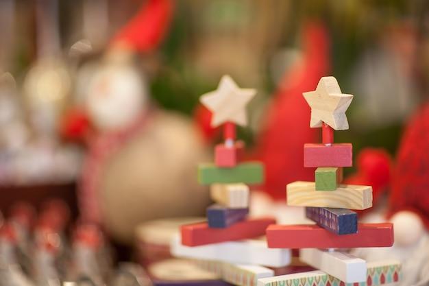 Kerst houten speelgoed in de vorm van opvouwbare piramide en ster op een onscherpe achtergrond