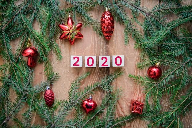 Kerst houten tafel met dennentakken tegen 2020