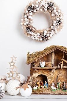 Kerst hygge interieur met kerststal met heilige familie en drie wijze mannen Premium Foto