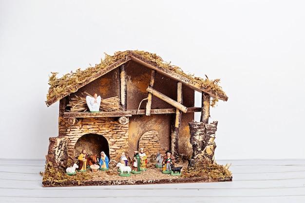 Kerst hygge interieur met kerststal met heilige familie en drie wijze mannen