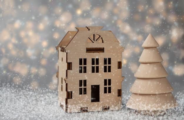 Kerst illustratie. stuk speelgoed houten huis met kerstboom en dalende sneeuw op onscherpe achtergrond