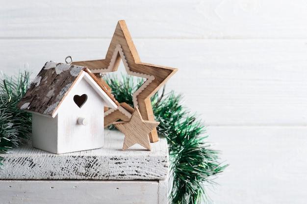 Kerst interieur decoratie whit vogelhuisje en sterren op witte rustieke oppervlak met kopie ruimte