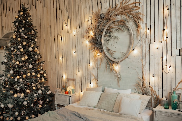 Kerst interieur van een slaapkamer met een kerstboom en slingers op de houten muur.