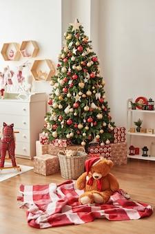 Kerst interieur van kinderkamer kerst in de kinderkamer. het zachte stuk speelgoed draagt op achtergrond van kerstboom