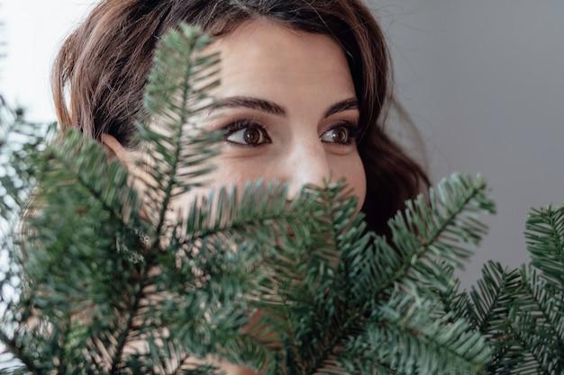 Kerst jong meisje make-up elegante dame houdt een tak van sparren in zijn handen mooie ogen