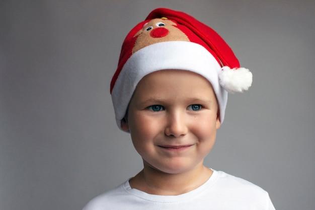 Kerst jongen. kerst achtergrond. een jongen in een kerstmuts. kopieer ruimte. winter vakantie.