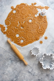 Kerst koekjes bakken sneeuwvlokken vorm. rauw deeg, koekjesmessen, deegroller.