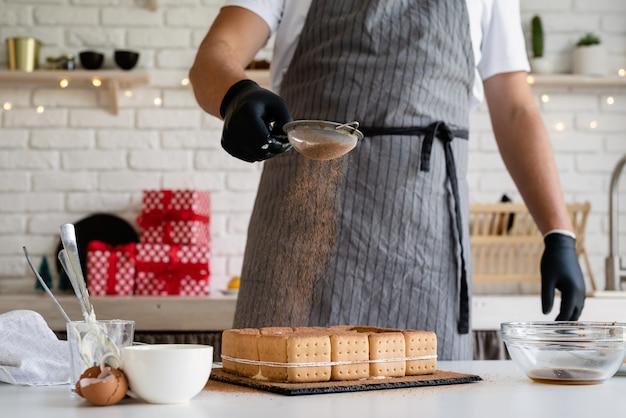 Kerst koken chef-kok koken dessert in de keuken cacaopoeder op het gieten