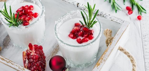 Kerst kokosnoot punch met granaatappel zaden en takjes rozemarijn op lichte achtergrond. selectieve aandacht. bovenaanzicht