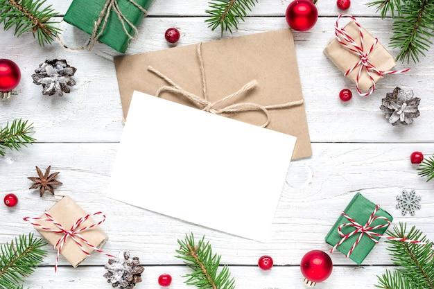 Kerst lege wenskaart in frame van dennentakken, ballen, rode bessen, geschenkdozen en kegels