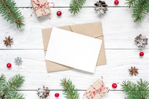 Kerst lege wenskaart in frame van dennentakken, rode bessen, geschenkdozen en kegels