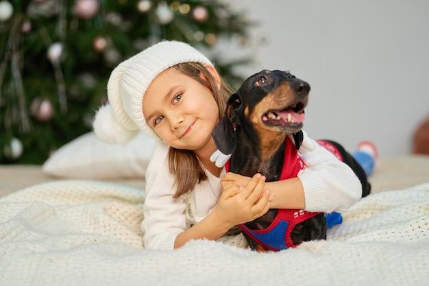 Kerst magisch sprookje. een klein meisje lacht met haar vriend, de teckelhond, dichtbij de boom