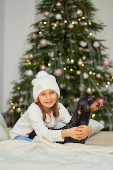Kerst magisch sprookje. een klein meisje lacht met haar vriend, een teckelhond, dichtbij boom.