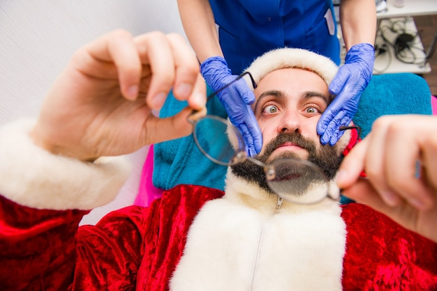 Kerst man in santa claus kleding in beauty spa. Premium Foto