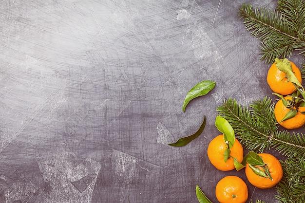 Kerst mandarijnen met bladeren en fir tree op zwart