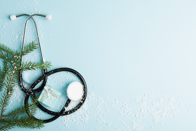 Kerst medisch concept met stethoscoop geschenkdoos en kerstboom op blauw