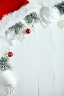 Kerst medisch coronavirus plat leggen, beschermend gezichtsmasker, pillen, antiseptica, decoratie op witte achtergrond, nieuwjaarsthema bovenaanzicht, minimalisme, platte lay-out, covid en gelukkig nieuwjaarsconcept