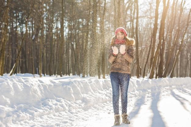 Kerst meisje buiten portret. winter vrouw waait sneeuw in een park.