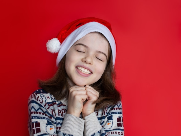 Kerst meisje in kerstmuts maakt wensen voor het nieuwe jaar en kerst kerstdromen