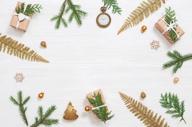 Kerst met gouden speelgoed en ballen, geschenk met natuurlijke thuja-takken, vintage zakhorloge