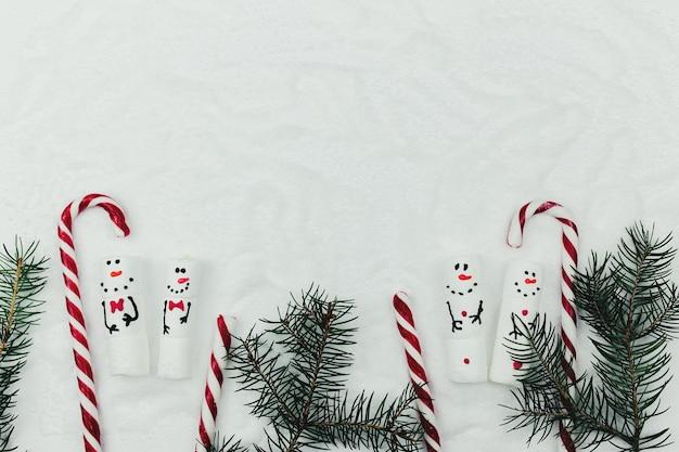 Kerst met marshmallow sneeuwpop op nep sneeuw met sparren en lolly.
