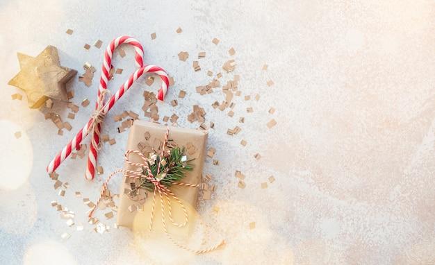 Kerst minimale creatieve achtergrond met geschenkdoos verpakt in kraftpapier, zuurstokken en kerststerkaars